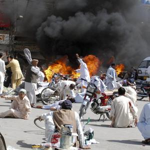 Injured people lie down on a road after an explosion in Quetta, Pakistan (AP)