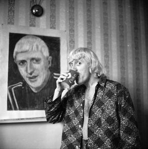 "FILE - OCTOBER 01, 2012:  ITV is scheduled to broadcast a documentary this Wednesday, ""Exposure: The Other Side of Jimmy Savile"", in which allegations are presented that the former television presenter and disc-jockey sexually abused teenage girls. 4th February 1965:  Disc-jockey, Jimmy Savile poses by a portrait of himself, painted by a friend, while enjoying his regular breakfast of coke and a cigar in the Bloomsbury hotel room which he has made his home.  (Photo by Chris Ware/Keystone Features/Getty Images)"