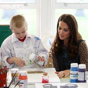 The Duchess helps Jaydn Proffitt, 7, with his painting at Rose Hill Primary School in Oxford