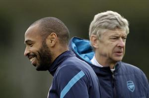 Arsenal's on loan former player, and the club's all time highest scorer, Thierry Henry, left, stands near the club's French manager Arsene Wenger during a training session at the club's facilities in London Colney, England, Tuesday, Feb. 14, 2012.  Arsenal are due to play AC Milan in the first leg of their Champions League last 16 soccer match in Milan on Wednesday