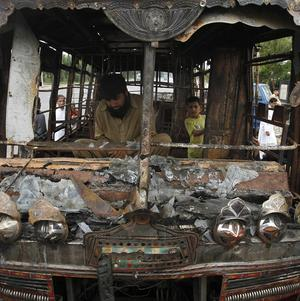 People look at a bus after it was set on fire by protestors in Karachi (AP)