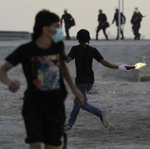 Anti-government protesters throw petrol bombs at riot police firing tear gas during clashes in Salmabad (AP)