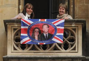 LONDON, ENGLAND - APRIL 28:  Two women display a British flag bearing a portrait of Prince William and Kate Middleton from a balcony of The Sanctuary next to Westminster Abbey a day ahead of the Royal Wedding on April 28, 2011 in London, England. Millions of people the world over are expected to watch live broadcasts of the wedding on television in what is becoming the most talked about event of the year.  (Photo by Sean Gallup/Getty Images)