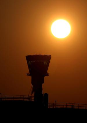 The sun sets behind the control tower of Heathrow Airport
