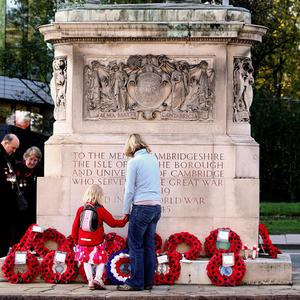 Members of the public view poppy wreathes following a service of remembrance in the centre of Cambridge