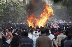 Protesters throw firebombs at riot police after police shot at protesters accompanying the funeral procession of an anti-government protester killed yesterday, in a street near Tahrir square in downtown Cairo, Egypt, Saturday, Jan. 29, 2011. Thousands of  protesters returned to Cairo's central Tahrir Square, chanting slogans against Egyptian President Hosni Mubarak and demanding his departure. (AP Photo/Ben Curtis)