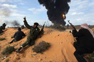 RAS LANUF, LIBYA - MARCH 09:  Libyan rebels take positions while fighting government troops as a facility burns on the frontline on March 9, 2011 near Ras Lanuf, Libya. The rebels pushed back government troops loyal to Libyan leader Muammar Gaddafi towards Ben Jawat.  (Photo by John Moore/Getty Images) *** BESTPIX ***