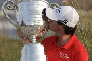 Rory McIlroy of Northern Ireland kisses the championships trophy for photographers after the final round of the PGA Championship golf tournament on the Ocean Course of the Kiawah Island Golf Resort in Kiawah Island, S.C., Sunday, Aug. 12, 2012. (AP Photo/Chuck Burton)