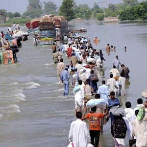 People and vehicles cross a flooded road in Baseera, in central Pakistan (AP)