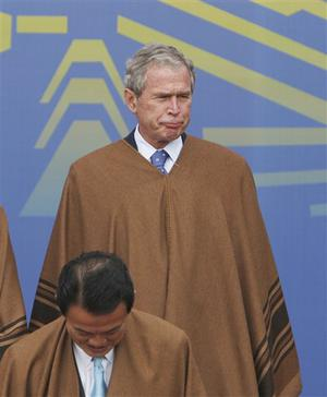 Wearing traditional Peruvian ponchos, President George W. Bush gestures as Japan's Prime Minister Taro Aso stands below before the official group photo of the 16th summit of the Asian Pacific Economic Cooperation, APEC, in Lima, Sunday, Nov. 23, 2008. (AP Photo/Lawrence Jackson)