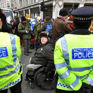 A protester in a wheelchair is confronted by police during a demo in which activists chained themselves together across Regent Street, London