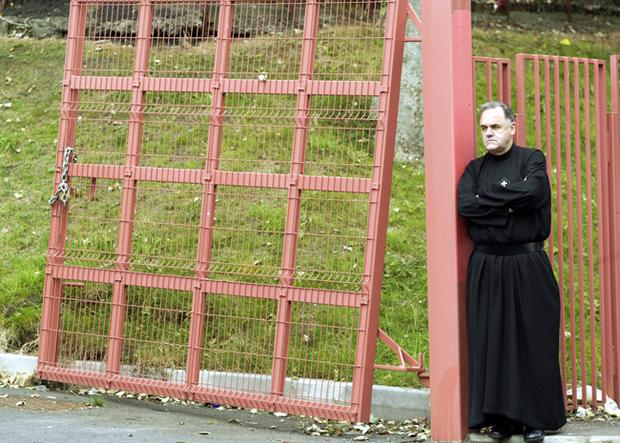 Fr Aidan Troy at the front gates of Holy Cross Girls School