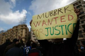 CAIRO, EGYPT - JANUARY 30:  A man in Tahrir Square holds a placard on January 30, 2011 in Cairo, Egypt. As President Mubarak struggles to regain control after five days of protests he has appointed Omar Suleiman as vice-president. The present death toll stands at 100 and up to 2,000 people are thought to have been injured during the clashes which started last Tuesday. Overnight it was reported that thousands of inmates from the Wadi Naturn prison had escaped and that Egyptians were forming vigilante groups in order to protect their homes after Police were nowhere to be seen on the streets. Broadcasts from the Al-Jazeera television network via an Egyptian satellite have now been halted.  (Photo by Peter Macdiarmid/Getty Images)