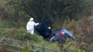 Prison officer David Black's black Audi A4 car lies in a ditch off the M1 motorway this morning after the attack.