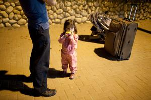 NETIVOT, ISRAEL - NOVEMBER 14:  (ISRAEL OUT )An Israeli man and child wait for a bus to leave town on November 14, 2012 in Netivot, Israel. Israel Defense Forces launched aerial attacks on targets in Gaza that killed the top military commander of Hamas, (Photo by Uriel Sinai/Getty Images)