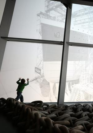BELFAST, NORTHERN IRELAND - MARCH 27:  A boy looks up at a window etching depicting the launch of The Titanic at the Titanic Belfast visitor attraction on March 27, 2012 in Belfast, Northern Ireland. The Titanic Belfast Experience is a new £90 million visitor attraction opening on March 31, 2012. One hundred years ago the maiden voyage of the ill-fated passenger liner Titanic sank after hitting an iceberg in the Atlantic on the night of April 14, 1911 with the loss of 1517 lives.  (Photo by Peter Macdiarmid/Getty Images)