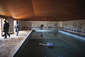 A Libyan man throws a piece of wood into the pool inside a destroyed palace owned by Libyan leader Moammar Gadhafi in the eastern town of Beyda, Libya, Monday, Feb. 28, 2011. The West moved to send its first concrete aid to Libya's rebellion in the east of the country, hoping to give it the momentum to oust Gadhafi. But the Libyan leader's regime clamped down in its stronghold in the capital, quashing an attempt Monday to hold new protests as residents reported skyrocketing food prices from the crisis. (AP Photo/Tara Todras-Whitehill)