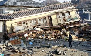 A residents of the seaside town of Yotsukura, northern Japan, walks past damaged homes Monday, March 14, 2011, three days after a giant quake and tsunami struck the country's northeastern coast. (AP Photo/Mark Baker)
