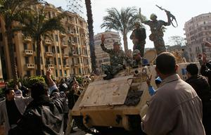 CAIRO, EGYPT - JANUARY 30:  Egyptian Army soldiers drive an armored personel carrier slowly through throngs of anti-government protesters in Tahrir Square January 30, 2011 in Cairo, Egypt.  As President Mubarak struggles to regain control after five days of protests he has appointed Omar Suleiman as vice-president. The present death toll stands at 100 and up to 2,000 people are thought to have been injured during the clashes which started last Tuesday. Overnight it was reported that thousands of inmates from the Wadi Naturn prison had escaped and that Egyptians were forming vigilante groups in order to protect their homes after Police were nowhere to be seen on the streets.  (Photo by Chris Hondros/Getty Images)