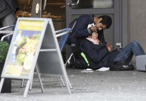 An injured woman is helped by a passerby, in a doorway in Oslo, Norway, Friday July 22, 2011, following an explosion that tore open several buildings including the prime minister's office, shattering windows and covering the street with documents and debris.  The Prime Minister is not hurt