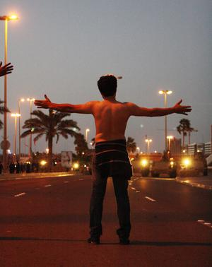 An anti-government protester faces off against the Bahraini army during a clash with security forces near the Pearl roundabout on February 18, 2011 in Manama, Bahrain
