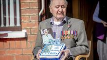 Billy with his medals, cake and card from the Queen