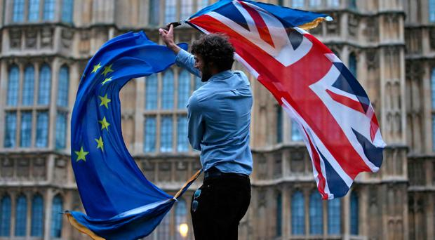 A man waves both a Union flag and a European Union flag together on College Green outside the Houses of Parliament