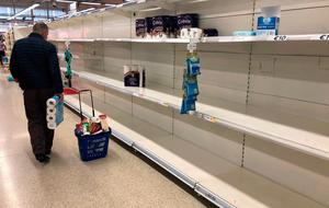 Empty supermarket shelves which were once filled with toilet rolls are now commonplace