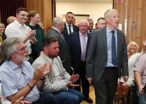 Gregory Campbell passes Gerry Adams in the audience as he walks to the stage for the debate.