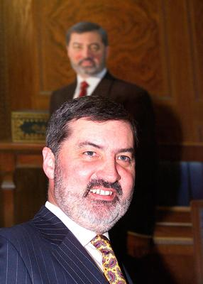 Lord Alderdice in front of a portrait of himself at Parliament Buildings