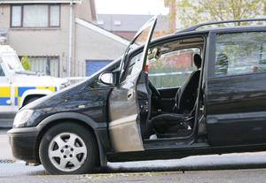 Police at the scene after a man was shot in the head as he sat in a car in the Shaw's Road area of west Belfast.