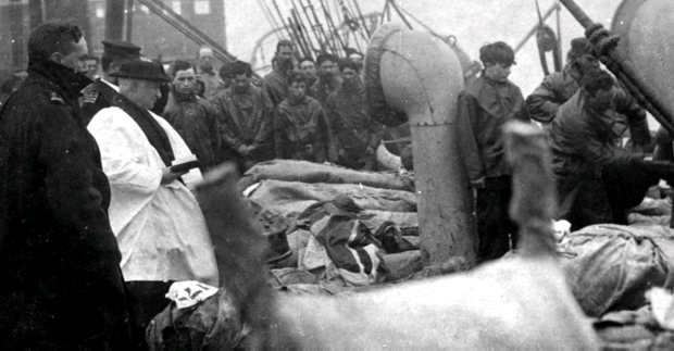 The photograph shows bodies in sacks piled three high on the deck of the CS Mackay Bennett, before being tipped overboard as the ship's priest conducts a service. Photo issued by Henry Aldridge and Son.