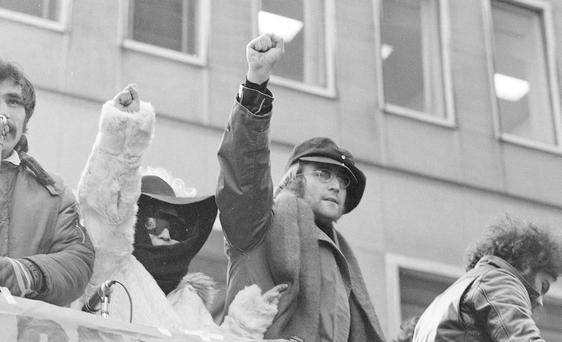John Lennon and his wife Yoko Ono raise their fists as they join a protest in this Feb. 5, 1972, file photo in front of British Overseas Airways Corp. offices in New York on Fifth Avenue. The demonstrators called for the withdrawal of British troops from Northern Ireland.
