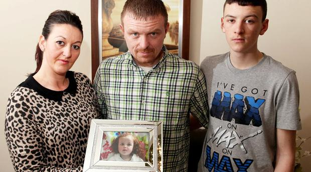 George and Gemma McNally pictured with their son Carl aged 16 holding a photo of their daughter Mila
