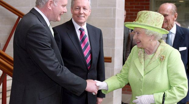 The Queen shakes hands with Northern Ireland's Deputy First Minister Martin McGuinness watched by First Minister Peter Robinson. Wednesday June 27, 2012