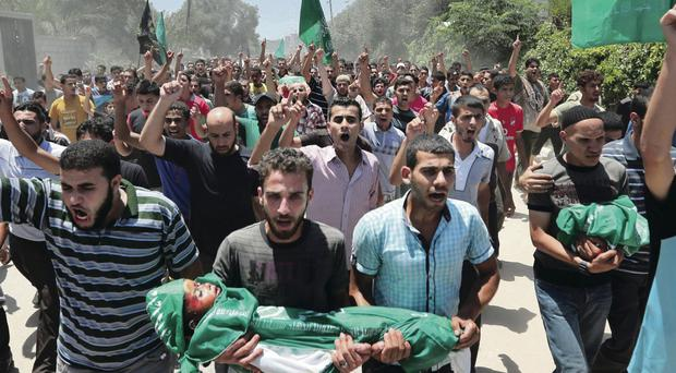 Palestinians carry three-year-old Mohammed Mnassragh, killed along with his family