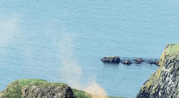 The scene at Carrick-a-Rede yesterday as a Royal Navy helicopter airlifts a man who became ill on the island