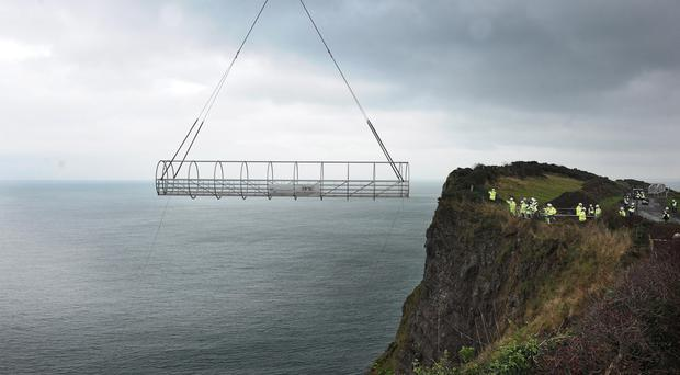 The tubular bridge section is hoisted on place at Gobbins cliff path