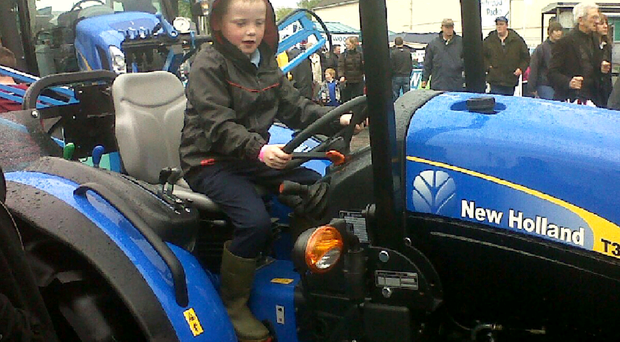Adam Gilmour playing on a tractor