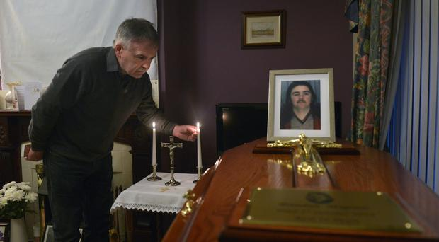 Kieran Megraw, brother of Brendan Megraw, one of 'The Disappeared', lights a candle as he welcomes home Brendan's remains
