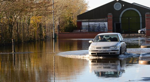 A driver negotiates a way through a flooded car park in Downpatrick last week