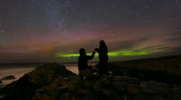 Martin McKenna gets down on one knee at the Giant's Causeway to propose to girlfriend Roisin Laverty with the stunning aurora borealis dancing in the Christmas Eve sky overhead