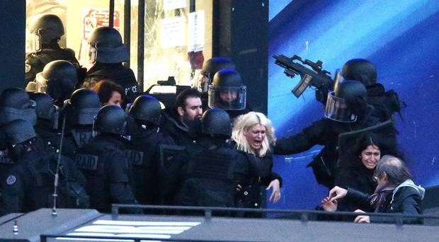 A woman runs from the Paris grocery store in tears as police storm the building in Porte de Vincennes on Friday