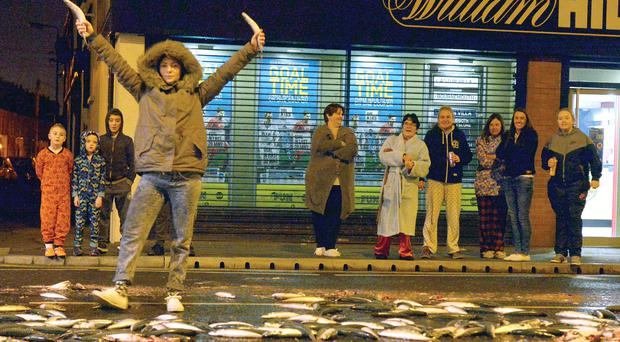 Residents inspect the fish spill at the weekend