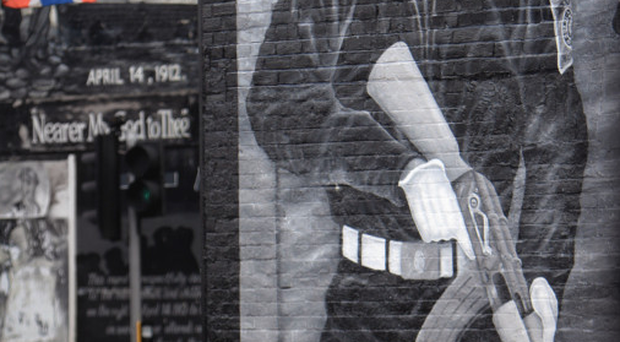 Shadow of a gunman: a boy plays football at a UVF mural on the Newtownards Road in east Belfast