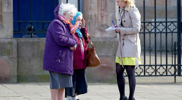 Reporter Deborah McAleese talks to parishioners outside St Peter's Cathedral yesterday