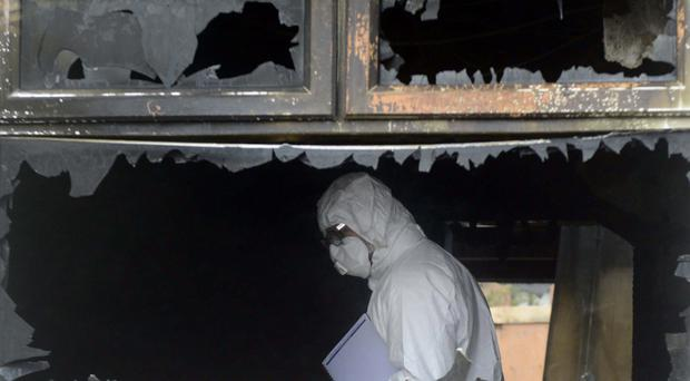A forensics officer inside the house in Jamaica Court