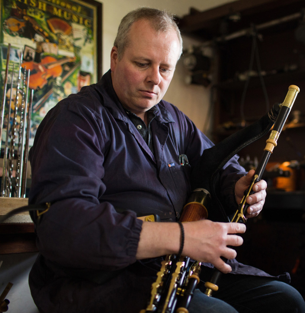 Martin Preshaw plays one of his pipes. Right, in his workshop and getting his award from Prince Charles