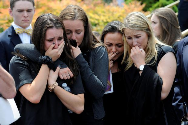 Mourners weep as the coffins of cousins Olivia Burke and Ashley Donohoe are placed in hearses at St Joseph's Catholic Church in Cotati, California