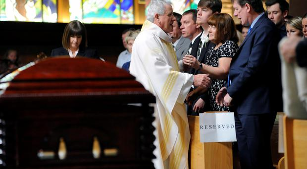 Monsignor Dan Whelton gives his condolences to the Burke family during funeral services for Olivia Burke and Ashley Donohoe at St Joseph's Catholic Church in Cotati, California, on Saturday